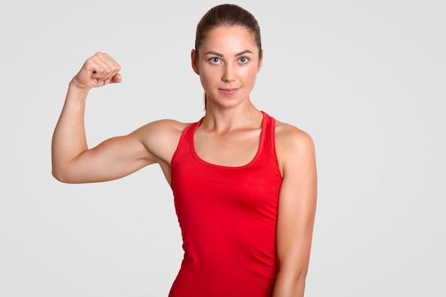 Tiro horizontal de auto-determinado jovem desportista em camiseta vermelha, mostra seus músculos, tem treinamento no ginásio todos os dias