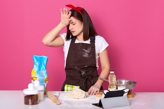 Tiro horizontal de cansada dona de casa exausta estar na cozinha