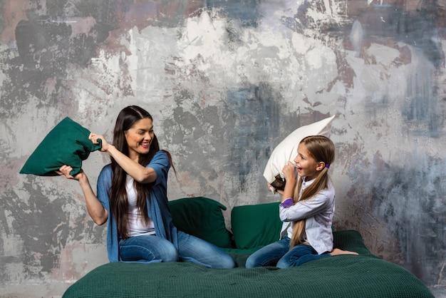 Tiro horizontal de diversão jovem mãe e sua filha brigam com almofadas na cama