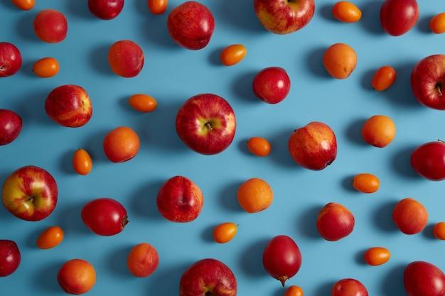 Tiro horizontal de doces suculentas maçãs vermelhas, pêssegos, tamarillo, cumquat sobre fundo azul. frutas saborosas. coleta de alimentos saudáveis ou diferentes tipos de frutas cultivadas organicamente. conceito de dieta de verão