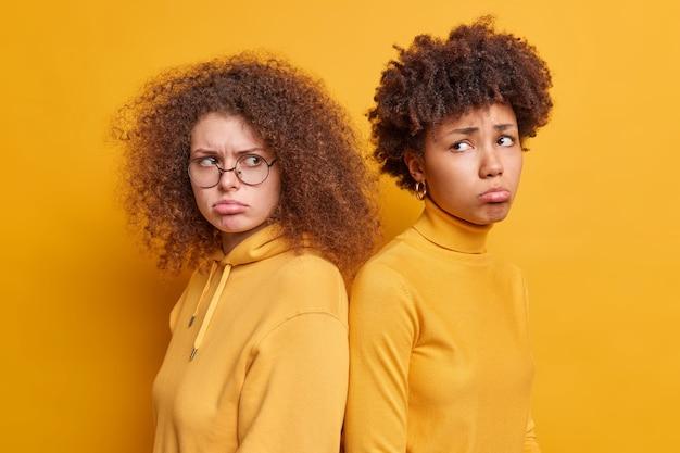 Tiro horizontal de duas mulheres diversas infelizes, de costas uma para a outra e não falam depois de brigarem com os lábios da bolsa vestidos com roupas casuais isoladas sobre a parede amarela. conceito de emoções negativas