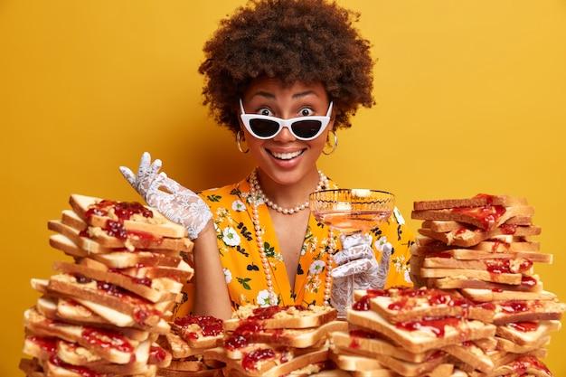 Tiro horizontal de feliz empresária encaracolada estando na festa corporativa, levanta a mão na luva, posa com coquetel, usa óculos escuros, fica perto de uma pilha de sanduíches contra a parede amarela.