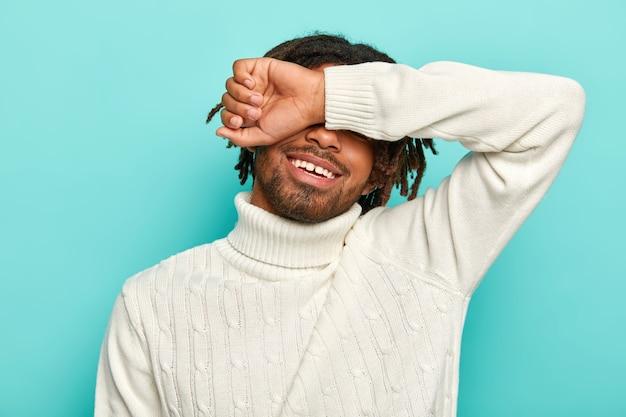 Tiro horizontal de feliz homem afro com dreadlocks, cobre os olhos, esconde o rosto com o braço, sorri feliz, usa um macacão branco, posa contra um fundo azul.