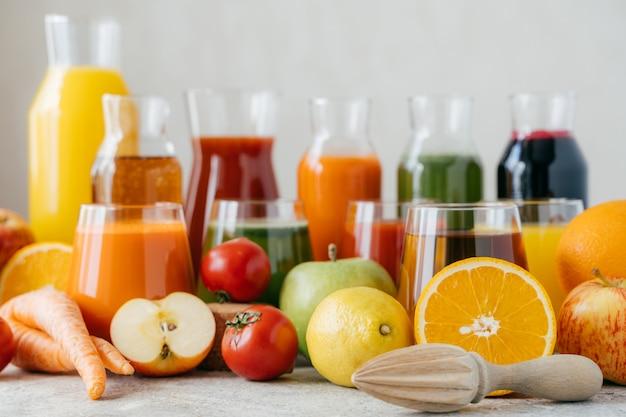 Tiro horizontal de frutas e legumes frescos na mesa branca, frascos de vidro de suco e espremedor de frutas laranja.