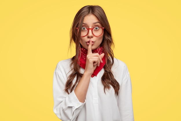 Tiro horizontal de garota secreta faz gesto de silêncio, mantém o dedo indicador sobre os lábios, pede para não espalhar boatos, posa contra a parede amarela. pessoas, segredo, conceito de conspiração. pessoas e linguagem corporal
