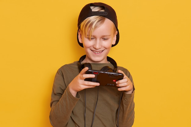 Tiro horizontal de garotinho vestindo boné preto e verde com capuz, posando com celular nas mãos, elegante garoto jogando jogos online.