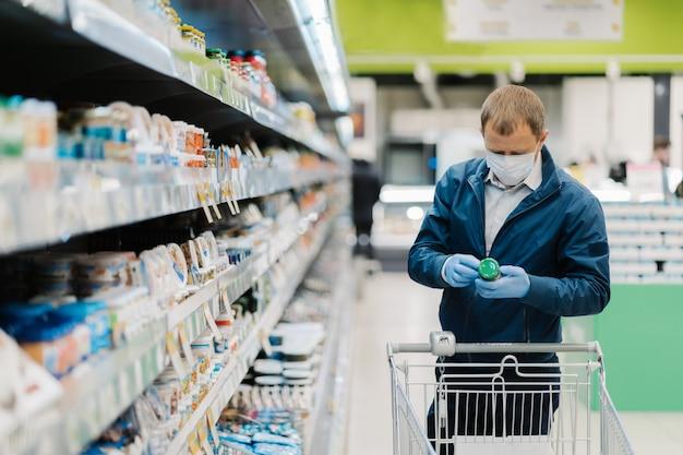 Tiro horizontal de homem adulto usa máscara protetora, lê o rótulo do produto, faz compras durante o surto de coronavírus, compra comida necessária na loja local. pessoas, vírus, doença, conceito de compra