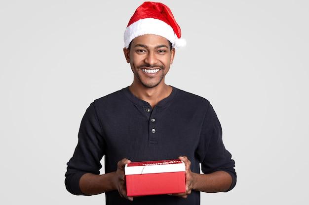 Tiro horizontal de homem alegre com sorriso, usa chapéu de papai noel, segura a caixa de presente vermelha, feliz em receber presentes
