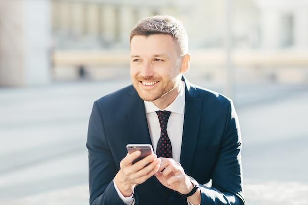 Tiro horizontal de homem atraente com expressão pensativa alegre, usa telefone celular moderno