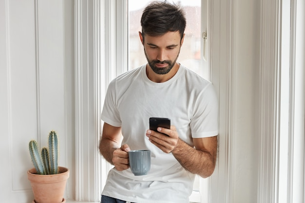 Tiro horizontal de homem barbudo bonito usa dispositivo de telefone inteligente moderno, bebe bebida quente, posa perto do peitoril da janela interior.