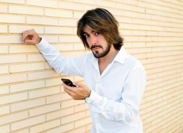 Tiro horizontal de jovem atraente, com cabelos longos, barba, camisa branca, encostado na parede, segura um smartphone na mão e parece