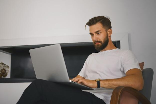 Tiro horizontal de jovem freelancer masculino bonito com barba espessa, sentado na poltrona com o computador portátil genérico, trabalhando remotamente de casa. conceito de pessoas, dispositivos, tecnologia e comunicação