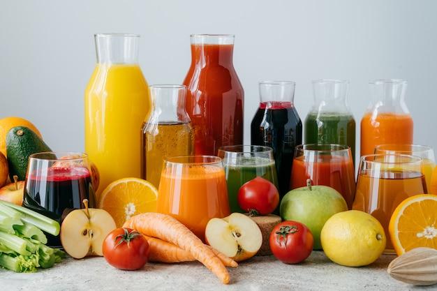 Tiro horizontal de legumes e frutas espremidos em garrafas de vidro.
