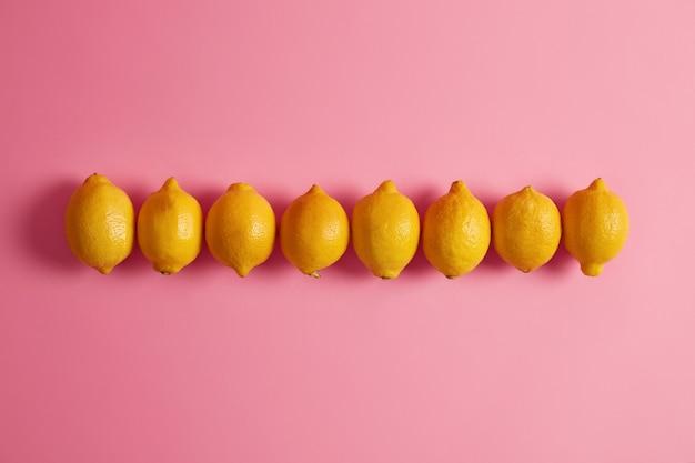 Tiro horizontal de limões inteiros amarelos dispostos em uma linha contra um fundo rosa. frutas cítricas são boas fontes de vitamina c e ácido fólico. ingrediente para fazer água saudável, limonada ou guarnição de alimentos