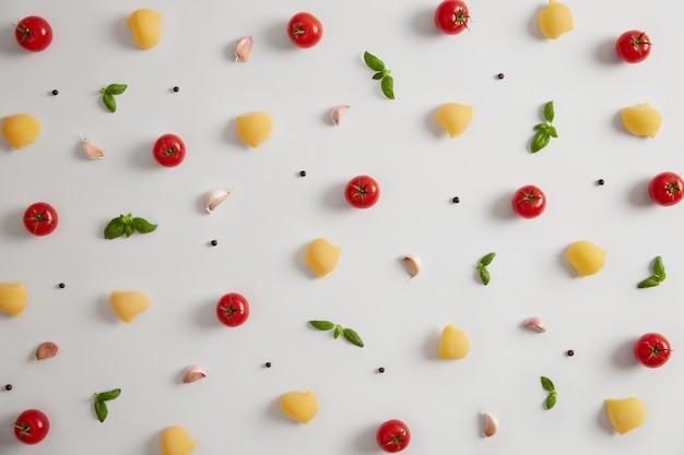 Tiro horizontal de macarrão com casca orgânica com saborosas ervas aromáticas italianas e especiarias, vegetais frescos maduros para cozinhar macarrão, fundo branco. estilo de vida de energia saudável. prato gourmet vegetariano