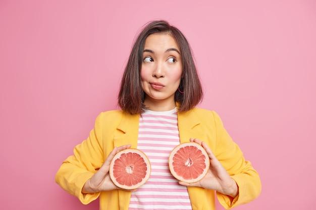 Tiro horizontal de mulher asiática pensativa detém duas metades de toranja concentradas e usa roupas elegantes isoladas sobre a parede rosa. nutrição natural e conceito de frutas cítricas suculentas.