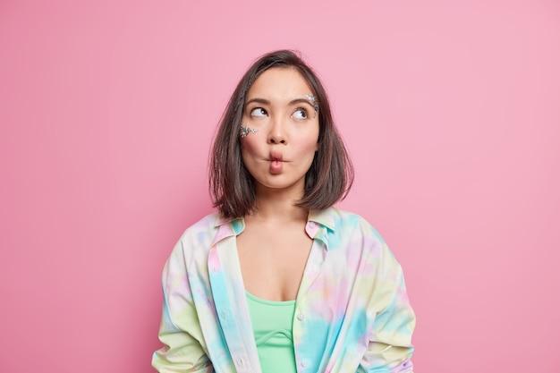 Tiro horizontal de mulher asiática pensativa faz bobagem de lábios de peixe concentrados acima, vestido com camisa colorida isolada sobre parede rosa sendo infantil. conceito de expressões faciais