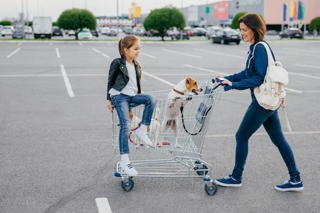 Tiro horizontal de mulher feliz carrega mochila, vestida com roupas jeans