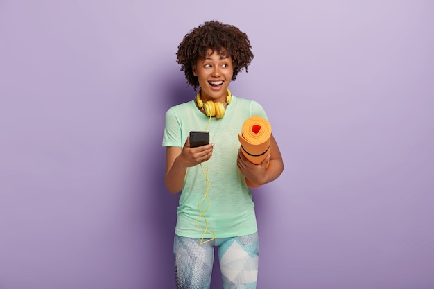 Tiro horizontal de mulher feliz fitness encaracolado ouve música através de fones de ouvido e smartphone durante o treino, carrega karemat enrolado, vestido com camiseta e leggings. pessoas, conceito de exercício