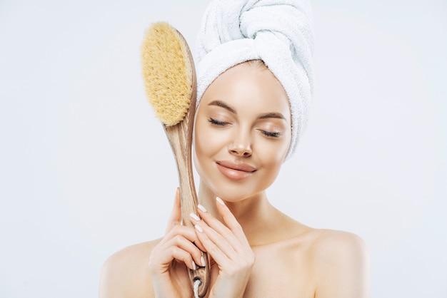 Tiro horizontal de mulheres satisfeitas fica com os olhos fechados, segura uma grande escova de banho para massagear a pele, gosta de tratamentos higiênicos em casa, isolado no fundo branco. beleza, cuidado, esfoliação