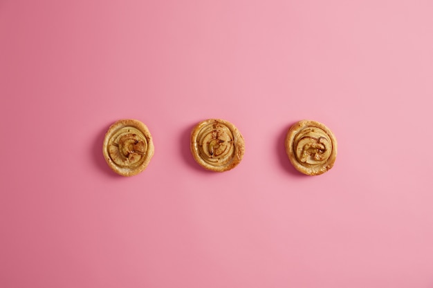 Tiro horizontal de pãezinhos de canela redemoinho caseiros frescos isolados no fundo rosa. conceito de dente doce, tentação e junk food. sobremesa deliciosa. quebrando a dieta. deliciosos pãezinhos açucarados.