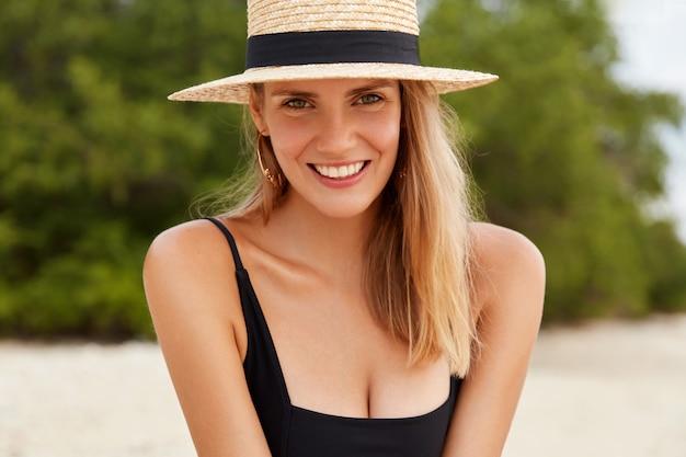 Tiro horizontal de poses positivas de mulher jovem e bonita na praia de areia, mostra o sorriso perfeito, sendo feliz por ter uma atmosfera calma na costa do oceano.