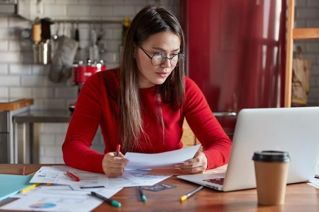 Tiro horizontal de trabalhador freelance ocupado lê dados de informação em papéis, verifica números no computador laptop, estuda gráficos em documentos, senta-se na área de trabalho no interior aconchegante da cozinha.