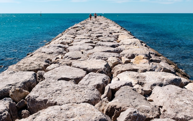 Tiro horizontal de um caminho de pedra em um corpo de água com pessoas andando sobre ele.