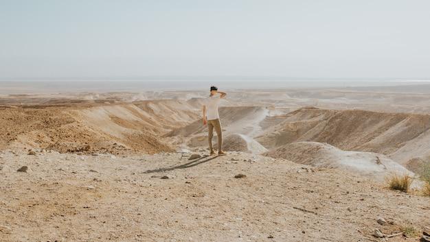 Tiro horizontal de um homem com uma camisa branca em pé na beira de uma montanha, apreciando a vista
