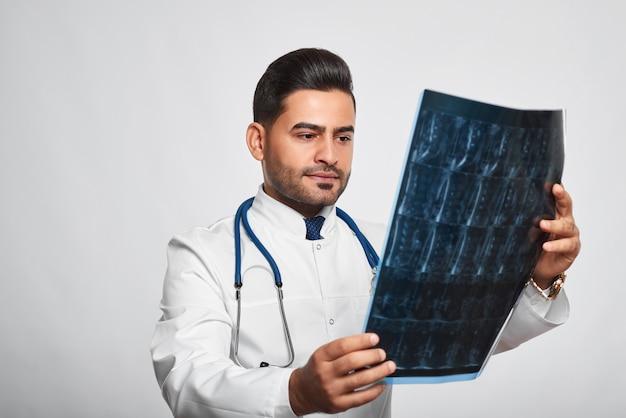 Tiro horizontal de um médico hispânico barbudo bonito examinando um conceito de profissionalismo de tratamento clínico de exame médico de exame de varredura de raio-x.