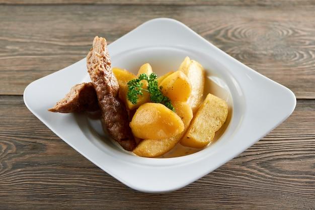 Tiro horizontal de um prato com fatias de batata frita e salsicha de frango em uma mesa de madeira jantar refeição almoço ceia carne comendo com fome delicioso vegetal grelhado assado.