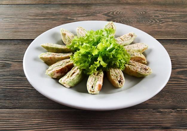 Tiro horizontal de um prato com rolos de panqueca com recheio cremoso decorado com salada em uma mesa de madeira restaurante café mercearia receita tradicional conceito delicioso de ingredientes.