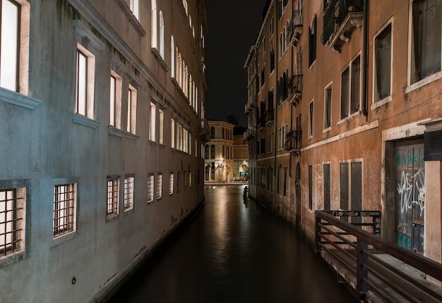 Tiro horizontal de um rio entre edifícios antigos, com belas texturas à noite em veneza, itália