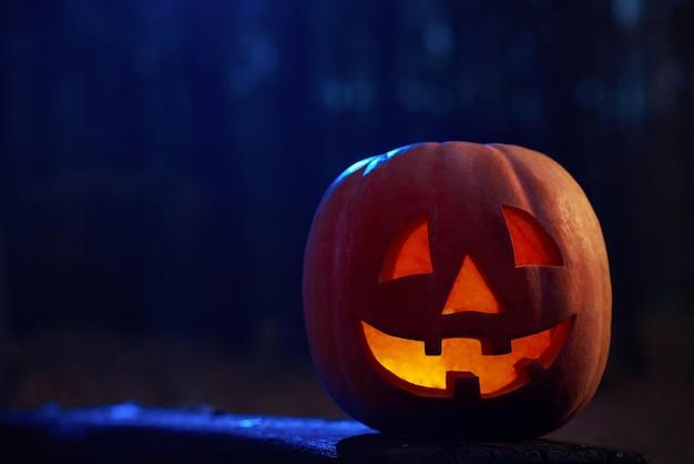 Tiro horizontal de uma abóbora lanterna de halloween de cabeça de jack na escuridão de uma vela misteriosa floresta de outono queimando dentro de copyspace.