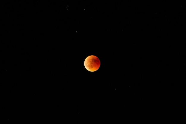Tiro horizontal de uma lua laranja e vermelha no céu escuro à noite