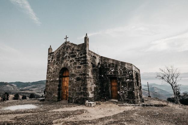 Tiro horizontal de uma pequena igreja velha em uma montanha