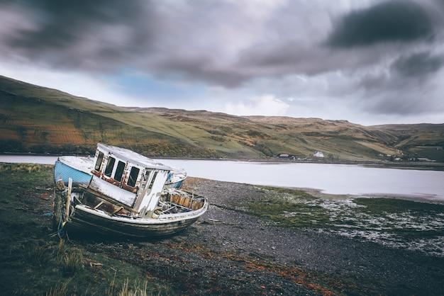 Tiro horizontal de uma praia com um barco abandonado perto da água