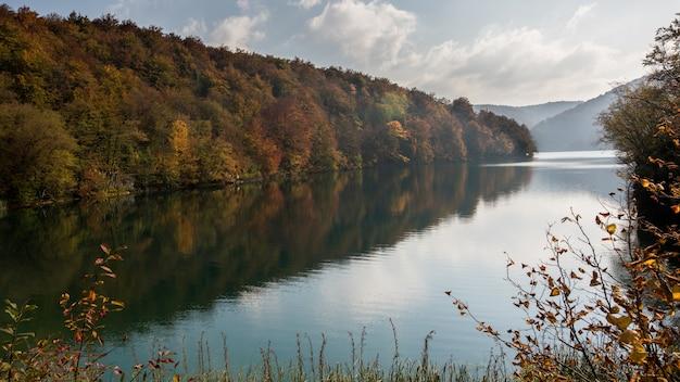 Tiro horizontal do belo lago plitvice no lago croácia, rodeado por árvores de folhas coloridas