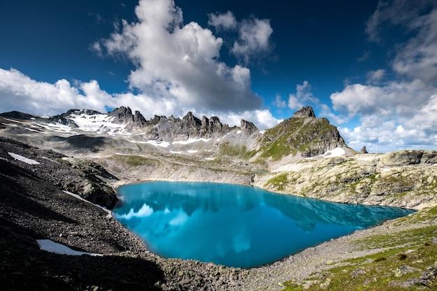 Tiro horizontal do corpo de água, rodeado por montanhas rochosas sob o lindo céu nublado