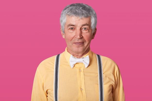 Tiro horizontal do homem maduro com cabelo cinza positivo com pele enrugada