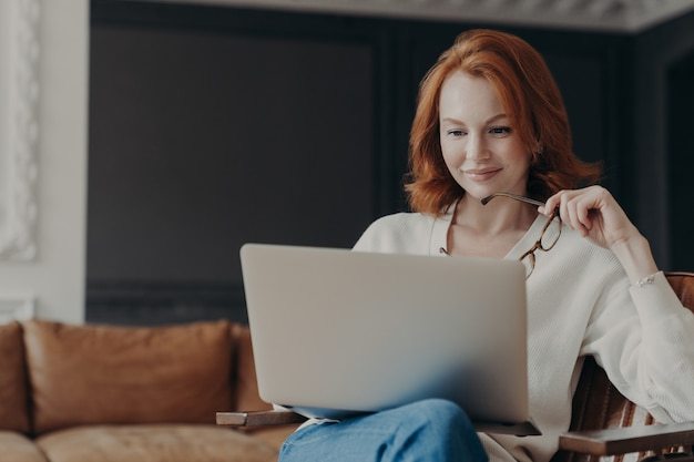 Tiro horizontal do professor mulher gengibre qualificado feliz trabalha à distância, verifica os alunos funciona via laptop, detém óculos, posa em apartamento acolhedor moderno. banco de dados de cheques para estudantes