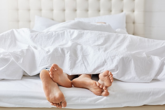 Tiro horizontal dos pés do casal sob roupa de cama branca na cama no quarto