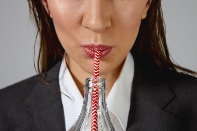 Tiro horizontal recortado de mulher com cabelo escuro loos, vestindo camisa branca e jaqueta, bebendo sofá de garrafa de vidro. jovem irreconhecível com roupas formais, bebericando uma bebida açucarada com canudo