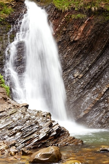 Tiro impressionante de cachoeira furiosa na floresta, branco ocupado fluxo de água que flui ao longo das falésias, aumentando o nível da água no rio da montanha