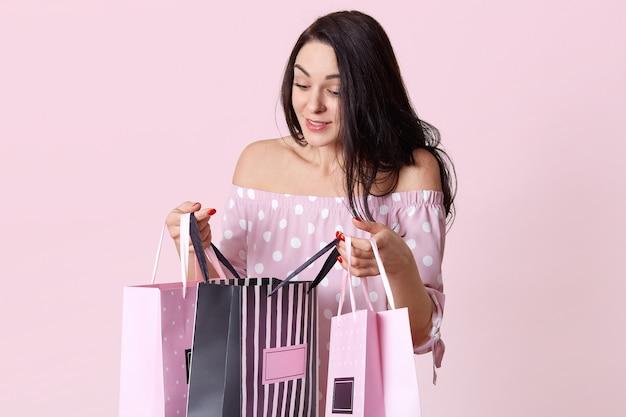 Tiro indoor de mulher bonita olha curiosamente para sacos de presente, recebe presentes de amigos no aniversário, usa vestido de bolinhas, coloca sobre parede rosa tem expressão intigada. conceito de compra