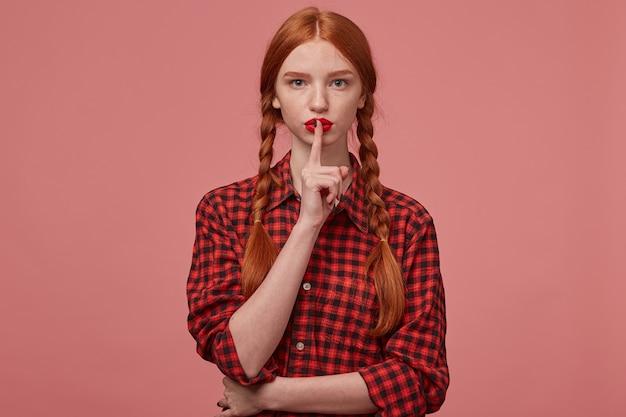 Tiro interno da fêmea de gengibre sério, mostrando o gesto de silêncio.