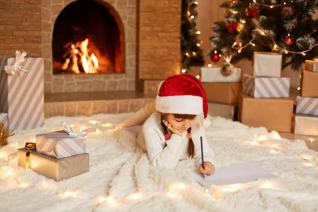 Tiro interno da menina bonita vestindo suéter branco e chapéu vermelho, deitada no chão em um tapete macio na sala decorada festiva, escrevendo uma carta para o papai noel.