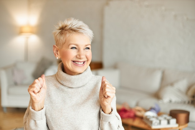 Tiro interno da moda feminina madura muito feliz em suéter de gola alta, desfrutando de notícias positivas, com expressão facial de êxtase, rindo e cerrando os punhos. conceito de sucesso e conquistas