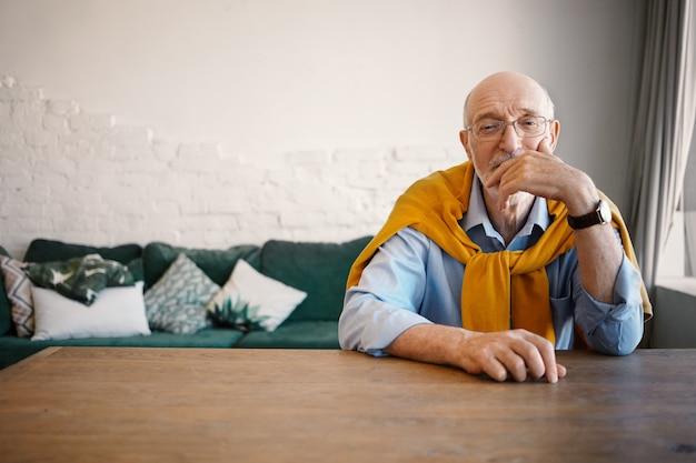Tiro interno de bonito homem maduro idoso com olhos sábios, sentado na mesa de madeira com sofá com expressão pensativa, tocando o rosto. pessoas, estilo de vida e idade