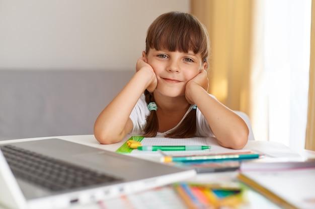 Tiro interno de feliz criança positiva do sexo feminino olhando para a câmera com expressão facial otimista, fazendo lição de casa, gosta de aulas online durante a quarentena.
